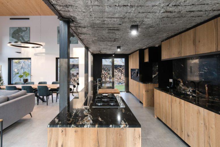 La cuisine est grande, elle est faite de bois teinté neutre et de pierre noire plus un plafond en béton