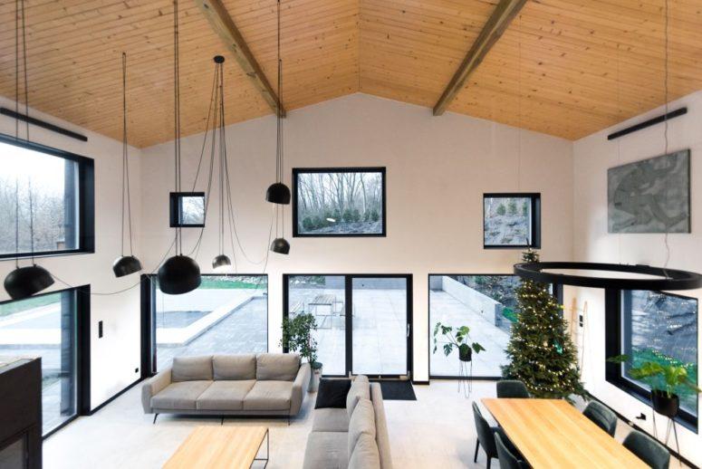 Le salon à double hauteur est encadré par de nombreuses fenêtres irrégulières qui apportent la lumière du soleil et de belles vues