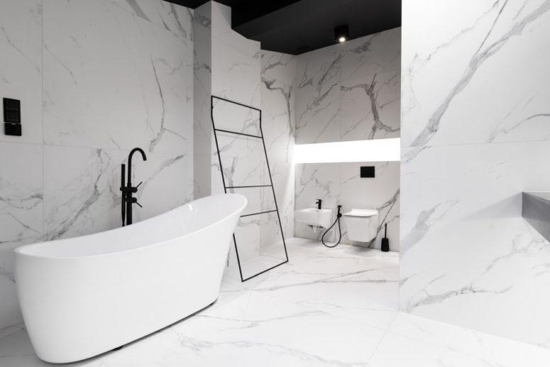 La salle de bain est revêtue de carreaux de marbre à grande échelle, tout est ici très minimaliste et raffiné