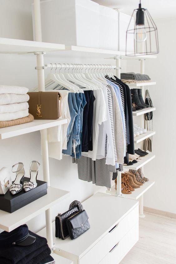 un petit placard de fortune élégant en blanc, avec des étagères, un support pour cintres et une commode pour les petites choses