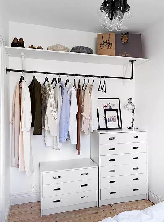un petit placard de fortune avec des commodes, un support pour cintres, une étagère ouverte en plein dans la chambre
