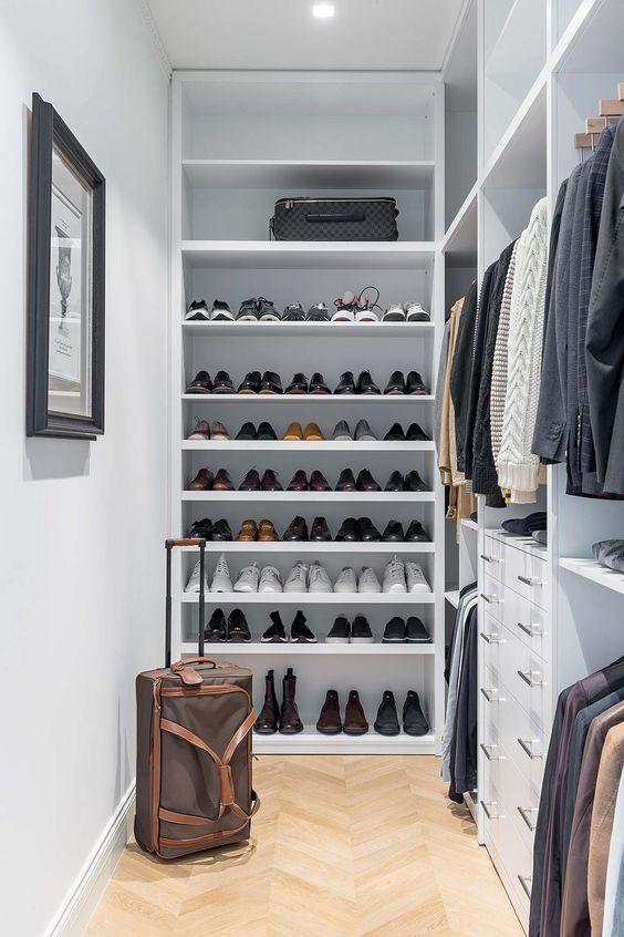 un petit placard masculin élégant en blanc, avec de nombreuses étagères à chaussures ouvertes, des supports avec cintres, des tiroirs intégrés et des lumières