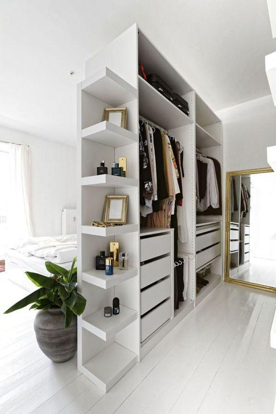 un petit placard ouvert en blanc avec des étagères, des supports et des tiroirs sert également de séparateur d'espace