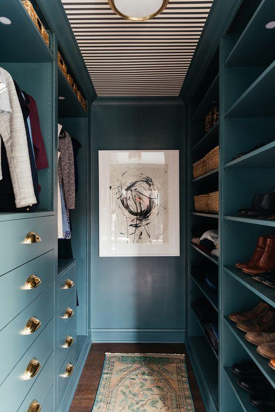un petit placard fait en bleu, avec d'élégants boutons dorés, un espace de rangement ouvert, des tiroirs et une lampe dorée sur le plafond rayé