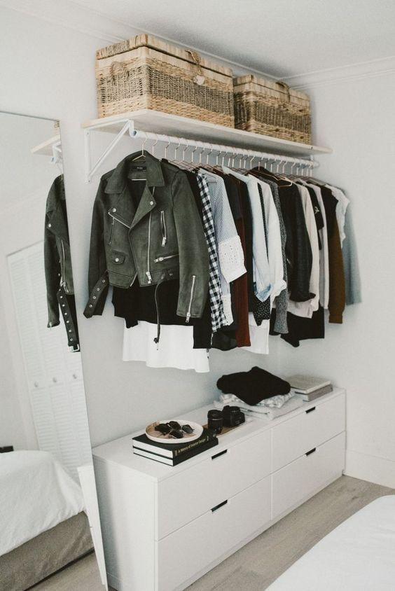 un petit placard de fortune chic avec un support avec des cintres, une commode, des paniers tressés peuvent être placés dans une chambre