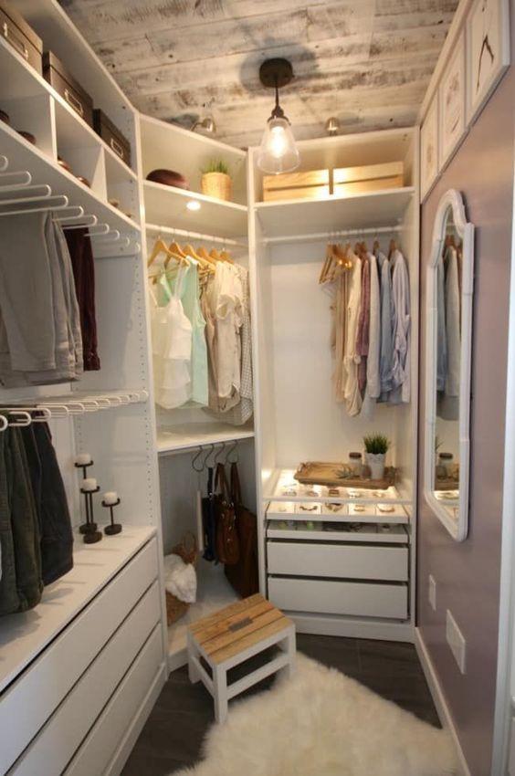 un petit placard de ferme avec des supports pour cintres, des étagères avec des boîtes, des tiroirs intégrés, un tabouret en bois et un plafond blanchi à la chaux