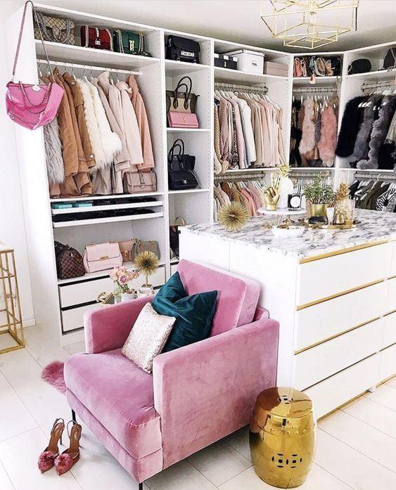 un petit placard glam avec beaucoup de supports avec cintres, étagères et tiroirs, une grande commode et une chaise rose