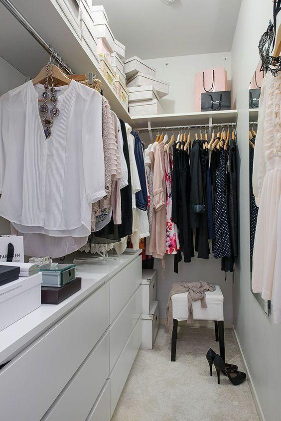 un petit placard contemporain en blanc, avec une grande étagère ouverte avec des boîtes, des commodes, des supports avec cintres et un tabouret