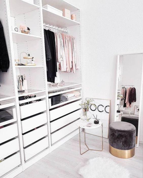 un petit placard glamour avec des étagères, un support pour cintres et quelques tiroirs, une grande fenêtre et un joli pouf en daim