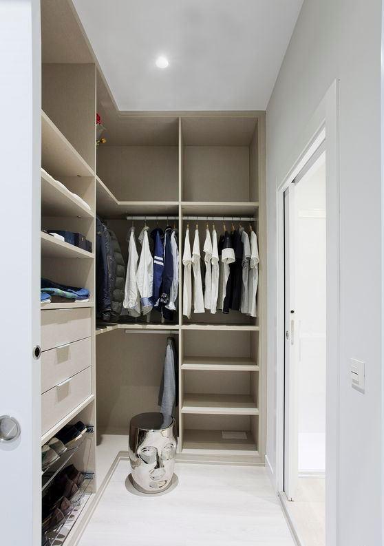 un petit placard minimaliste avec beaucoup d'espace de rangement ouvert, des tiroirs en forme de dôme et des supports pour cintres, un tabouret créatif et une porte coulissante en verre