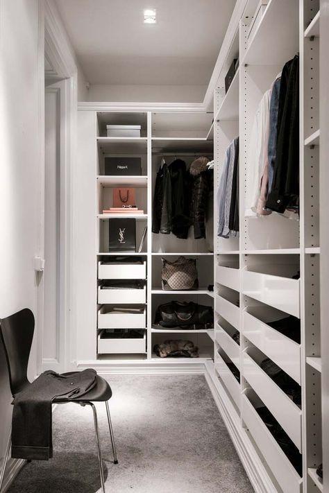 un petit placard minimaliste avec des supports pour cintres, de nombreux tiroirs, des étagères ouvertes et une seule chaise noire