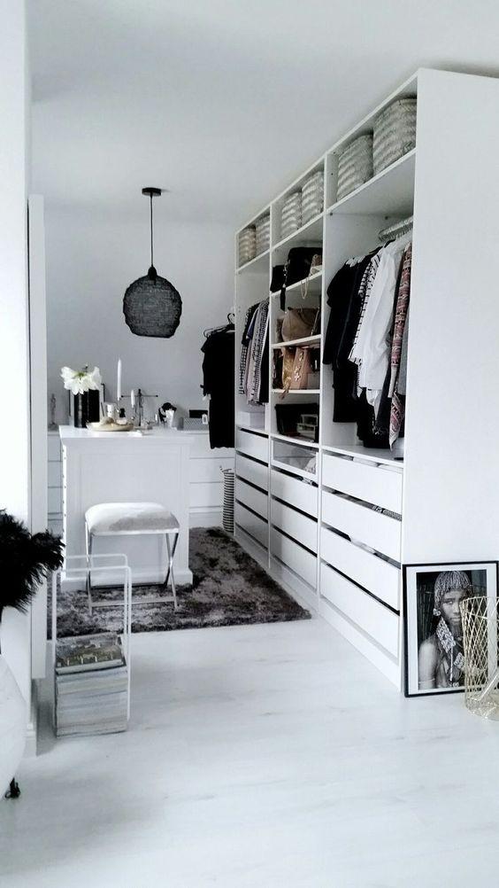 un petit placard blanc avec des supports, des étagères et de nombreux tiroirs, avec une petite table pour le maquillage et une suspension noire