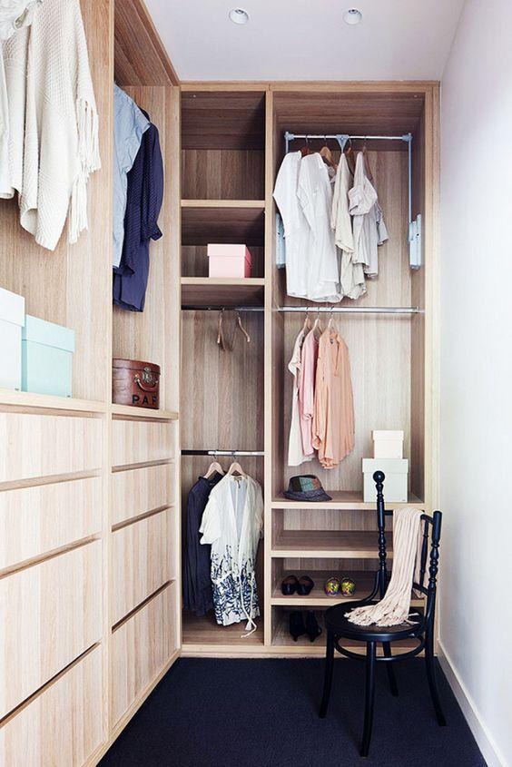 un petit placard élégant en bois teinté clair, avec des supports pour cintres, des étagères ouvertes, des tiroirs intégrés et une chaise noire
