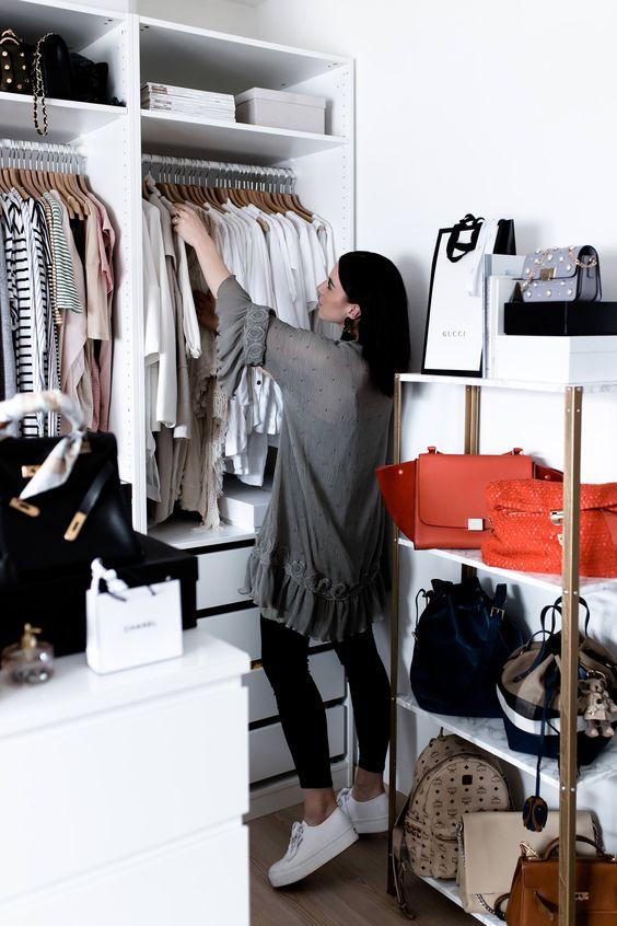 un petit placard en blanc, avec des étagères ouvertes, des tiroirs, des supports pour cintres, une commode et une unité de rangement ouverte pour les sacs