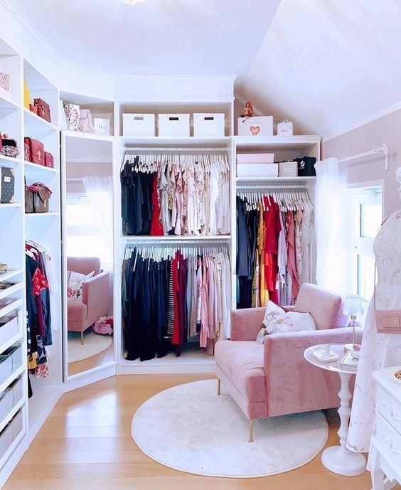 un petit placard mignon avec beaucoup de vêtements sur des cintres, des tiroirs pour les petites affaires et accessoires et des étagères pour les sacs plus une chaise rose