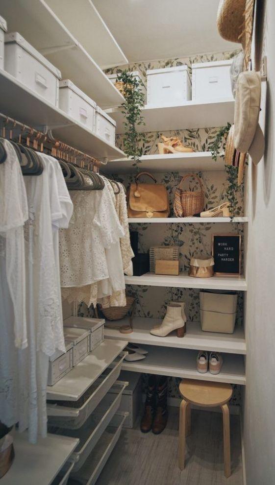 un petit placard de fille avec du papier peint botanique, une fausse plante en cascade, des étagères ouvertes, des casiers, des supports pour cintres et un tabouret en bois