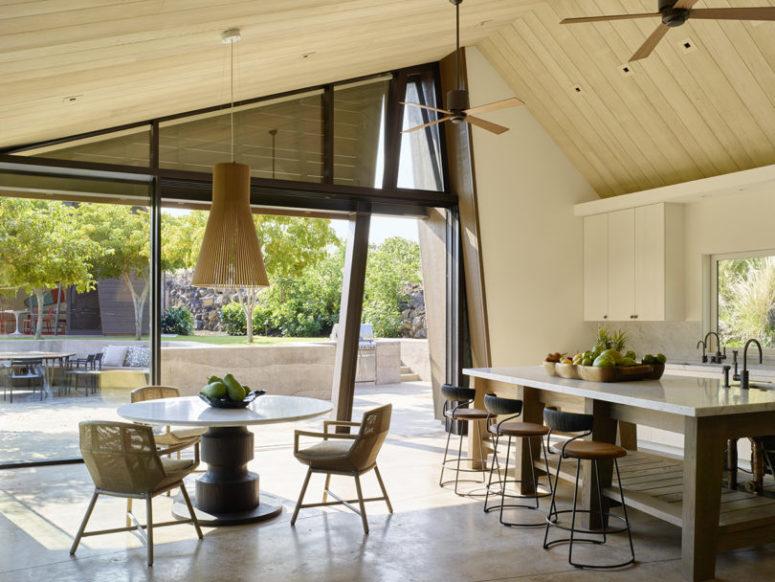 La cuisine est entièrement neutre et il y a une petite salle à manger avec une suspension en bois