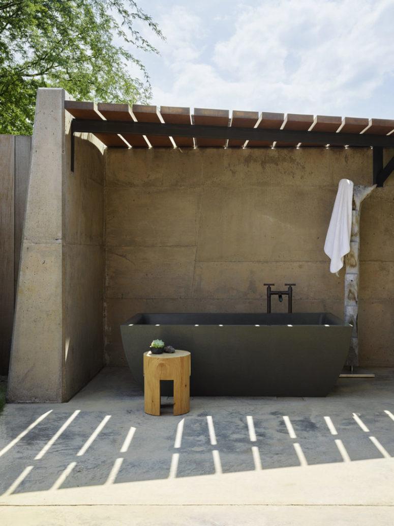 Il y a une salle de bain extérieure conçue en béton et avec une grande baignoire en pierre