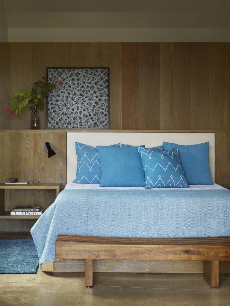 La chambre principale est faite avec beaucoup de bois naturel, avec un lit intégré et un banc, avec une jolie œuvre d'art