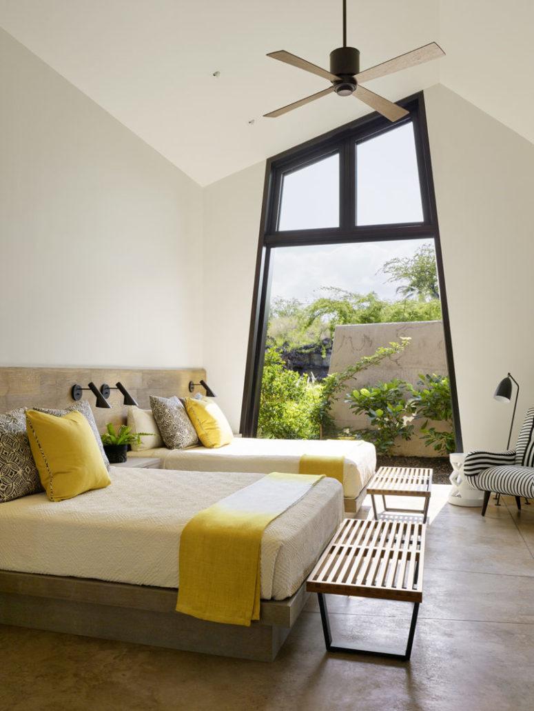 La chambre d'amis comprend deux lits, une literie colorée et une partie vitrée du mur qui permet d'entrer dans le jardin
