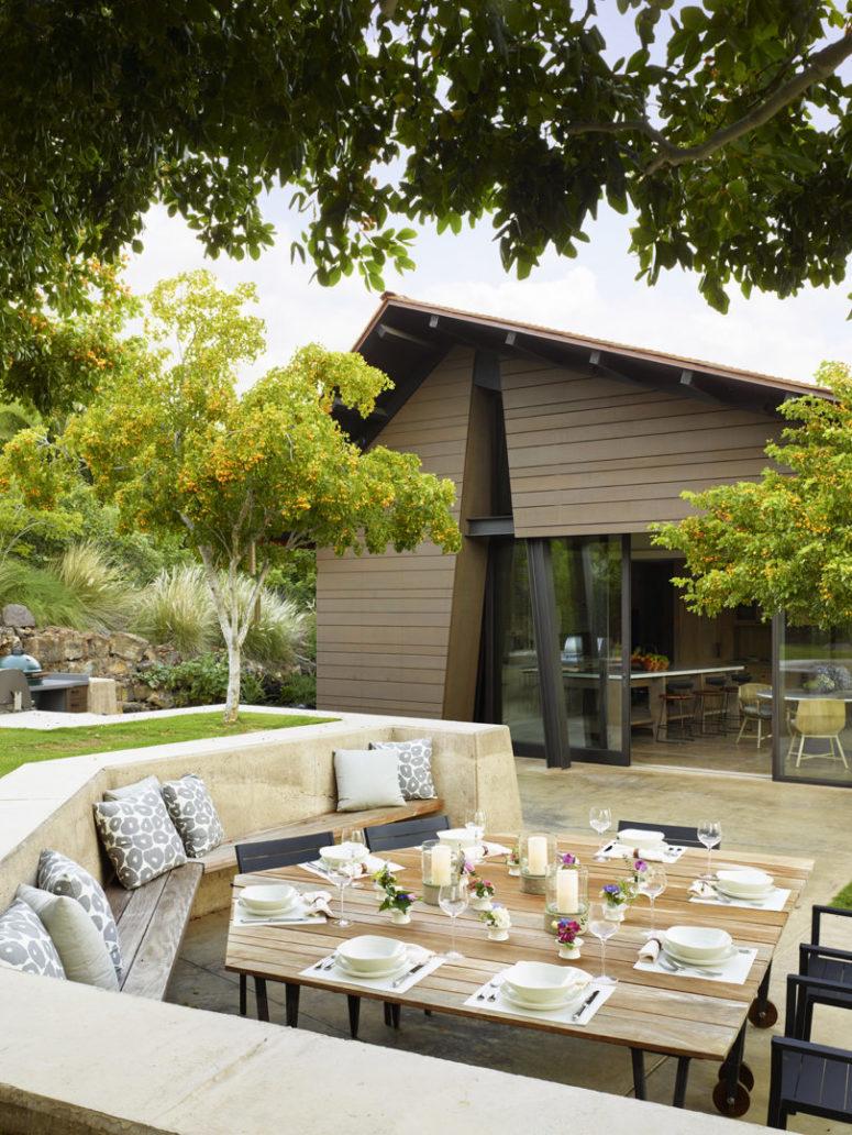 Il y a une autre terrasse avec un espace repas intégré et une table géométrique accrocheuse