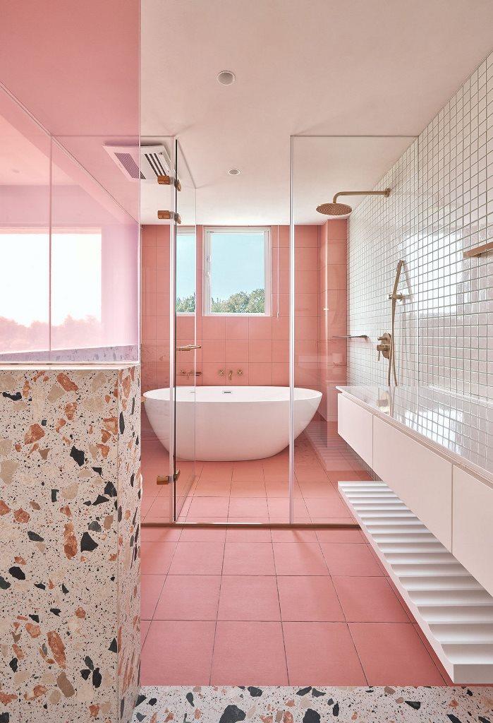 La salle de bain comprend également beaucoup de carreaux roses et neutres et de terrazzo