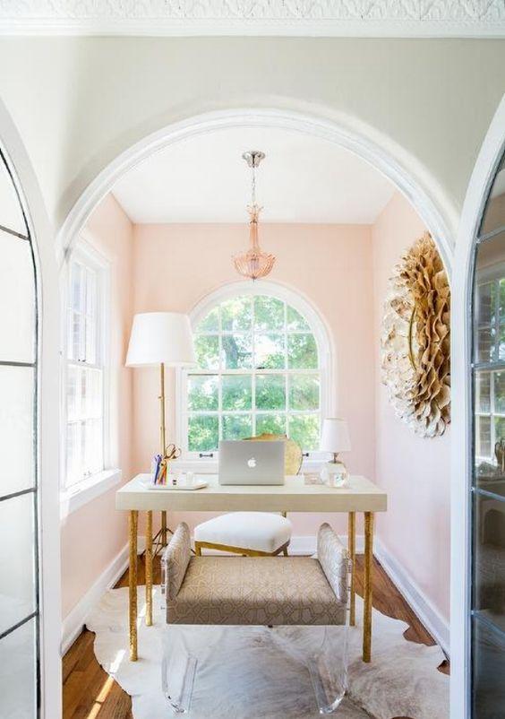 un coin bureau à la maison chic et confortable avec des murs rose clair, un lustre chic, un bureau simple et un banc tapissé et acrylique