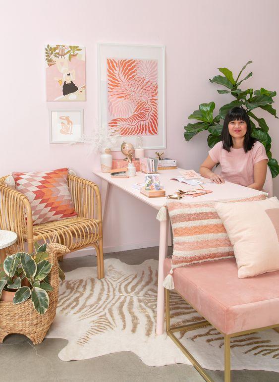 un bureau à domicile glam cool avec des murs rose clair, une chaise rose, un mur de galerie rose et un oreiller imprimé lumineux