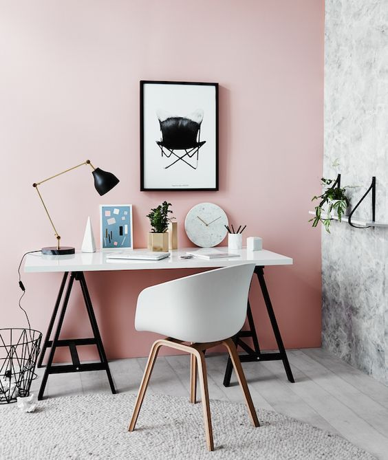un bureau à domicile audacieux avec un mur rose, un mur en marbre, des meubles en noir et blanc et une lampe de table