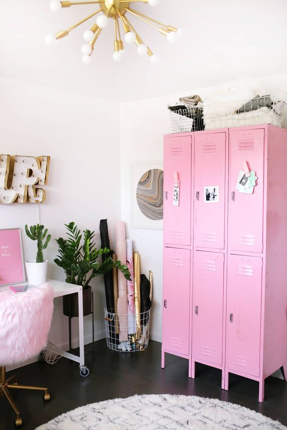 un bureau à domicile accrocheur avec une unité de rangement rose, une œuvre d'art rose et une chaise moelleuse ainsi que des touches dorées ont l'air super glam