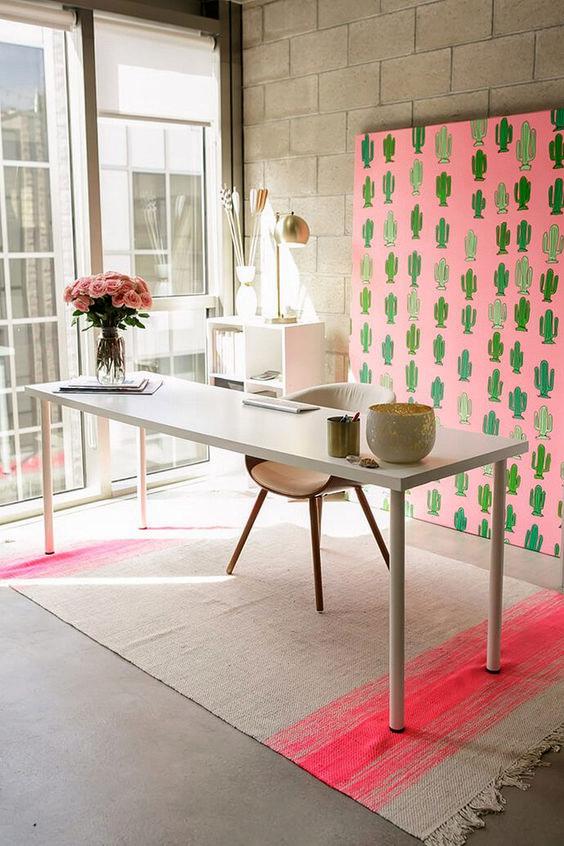 un bureau à domicile créatif avec une illustration de cactus rose, un tapis à rayures roses et des fleurs ainsi que des meubles neutres