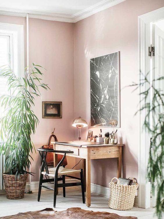 un bureau à domicile créatif avec des murs roses, des meubles en bois, de la verdure en pot et un tapis en peau d'animal semble inhabituel
