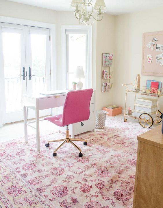 un joli bureau à domicile éclectique avec une chaise rose vif, un tapis rose à imprimé floral et quelques autres accessoires qui ajoutent une touche de fille