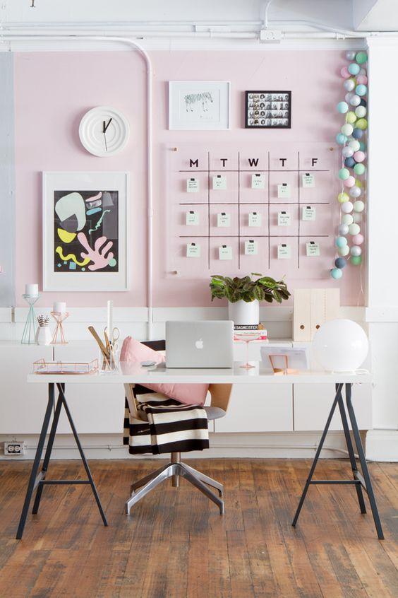 un bureau à domicile contemporain élégant avec des murs rose clair, un mur de galerie avec un calendrier, un bureau léger et des accessoires roses