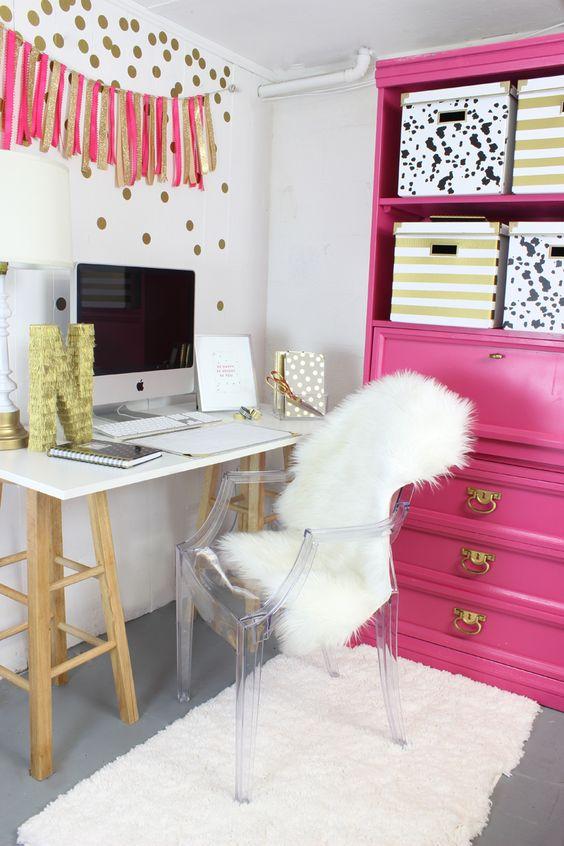 un bureau à domicile glam avec une unité de rangement rose vif et une guirlande de paillettes roses et dorées ainsi qu'une chaise en acrylique