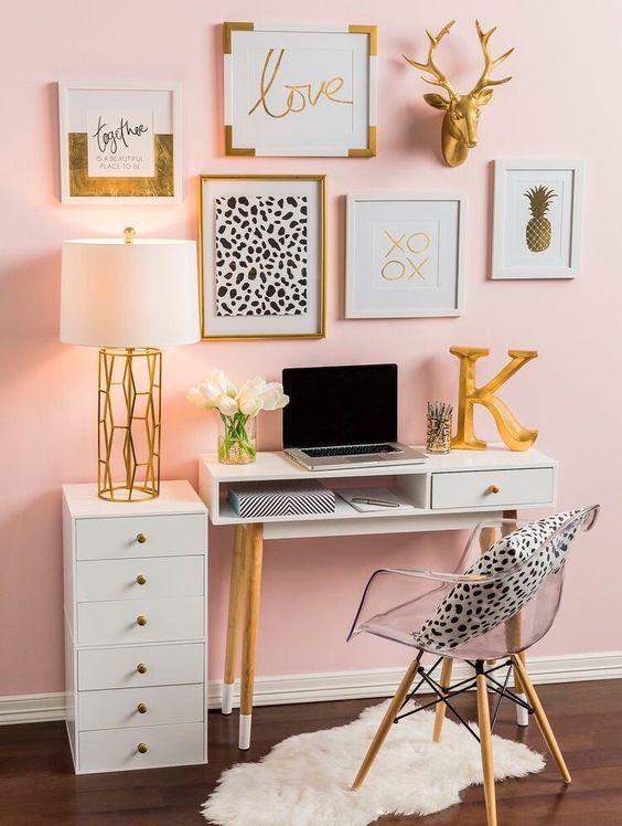 un bureau à domicile glam avec des murs roses, une chaise en acrylique, un joli mur de galerie en or, noir et blanc