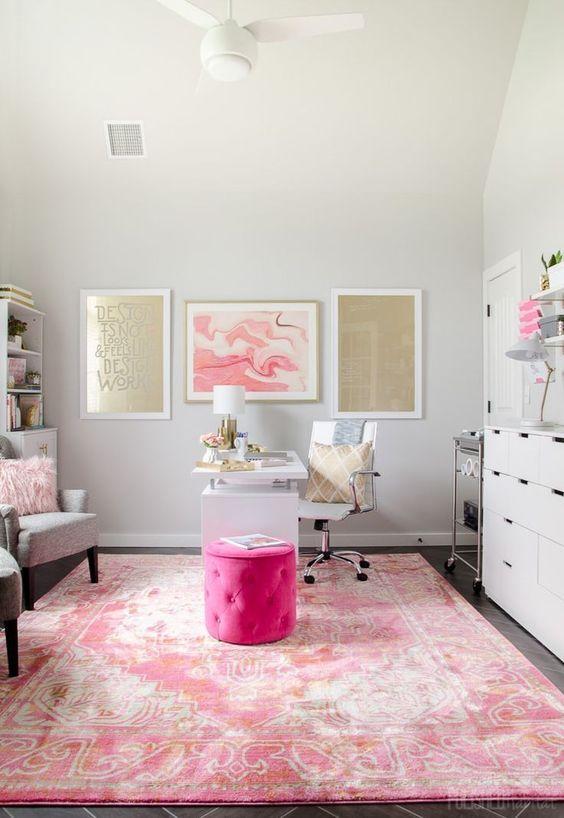 un bureau à domicile glamour avec un tapis imprimé rose, des murs de galerie dorés et roses, un pouf rose vif et un oreiller moelleux