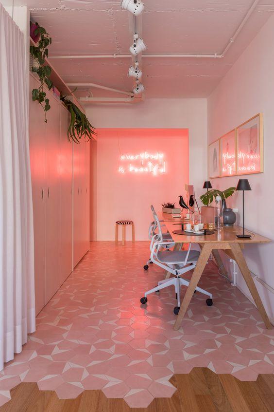 un bureau à domicile super moderne avec un mur rose et des néons, un mur de galerie rose, un sol carrelé rose et blanc et des unités de rangement élégantes