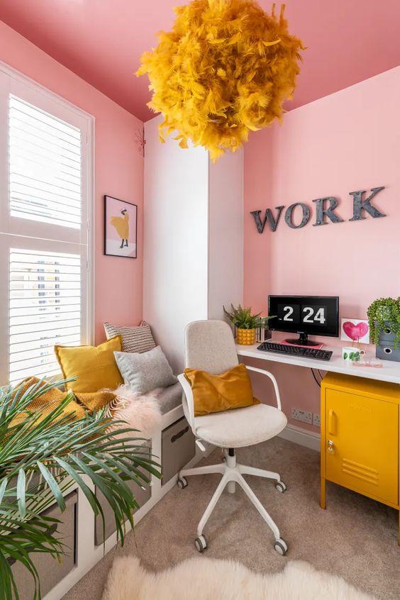un bureau à domicile super audacieux en rose, gris et moutarde, avec des murs roses et un plafond, avec des accessoires moutarde est un espace unique