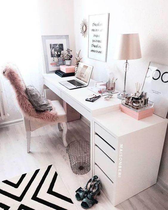 un bureau à domicile monochrome élégant avec une couverture en fausse fourrure, des accessoires roses et une lampe rose ainsi qu'un tapis graphique