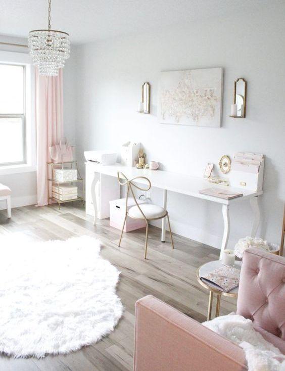 un bureau à domicile aéré et éthéré avec des murs blancs, des rideaux roses, des meubles roses et quelques accessoires ainsi qu'un lustre en cristal