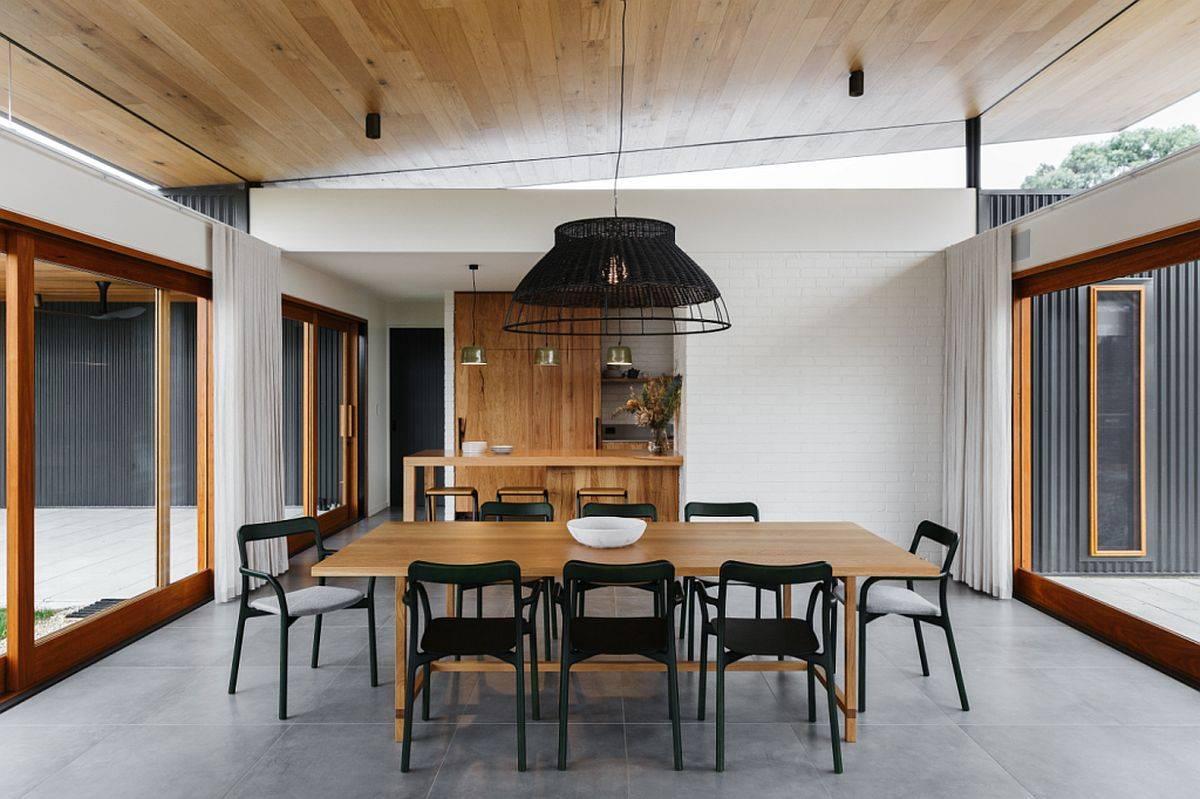 Salle-à-manger-moderne-de-la-maison-aussie-avec-sol-gris-portes-coulissantes-en-verre-et-table-en-bois-95577
