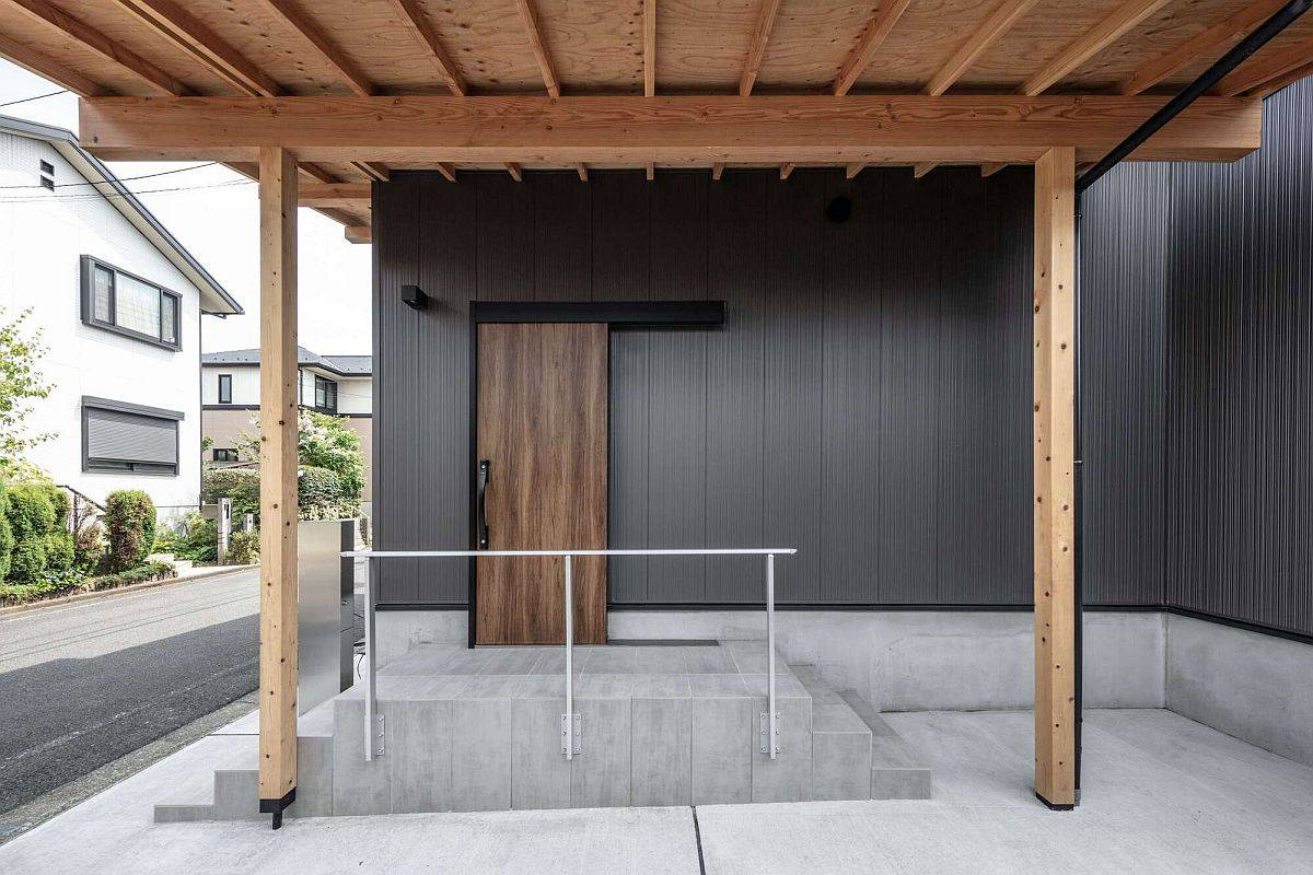 Entrée-de-la-maison-en-noir-avec-porte-en-bois-et-accents-simples-67667